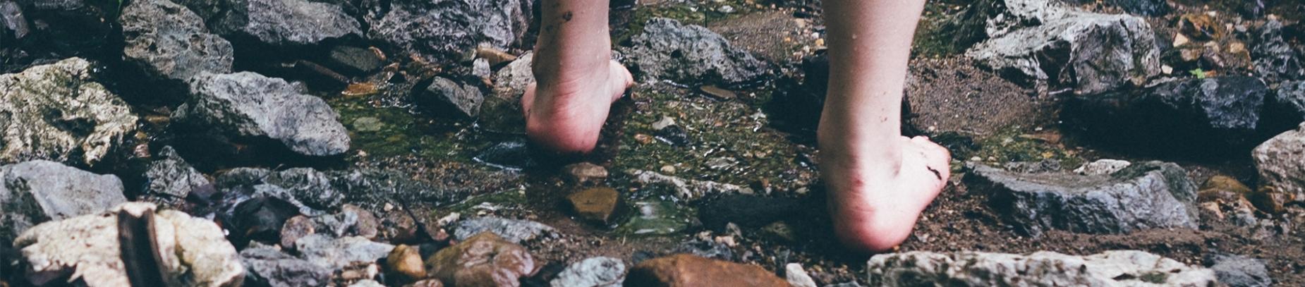 A person bare foot walking through a stream