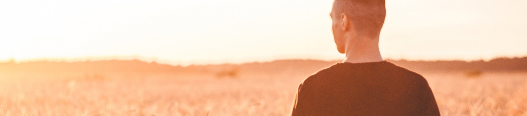 A guy stood in a field with the sun shining on him
