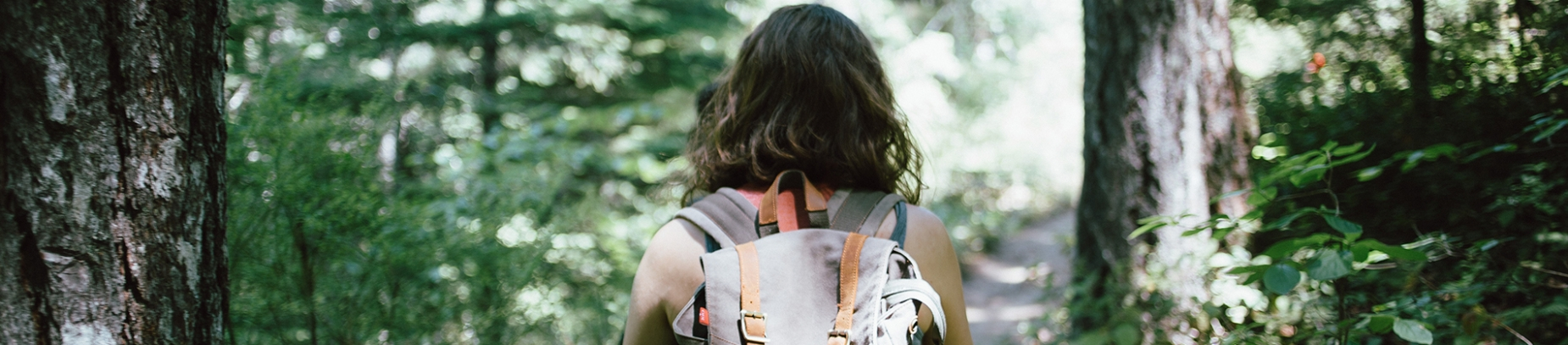 A women with a backpack walking through a forest