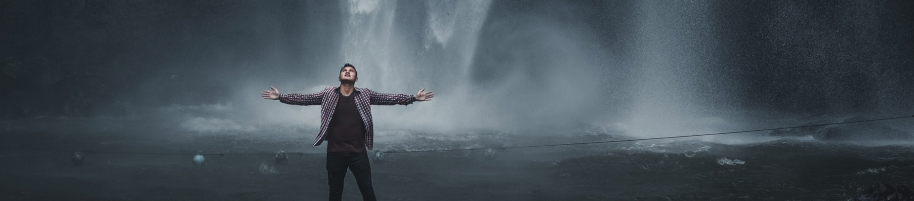 A man stood in front of a waterfall with his arms stretched out wide