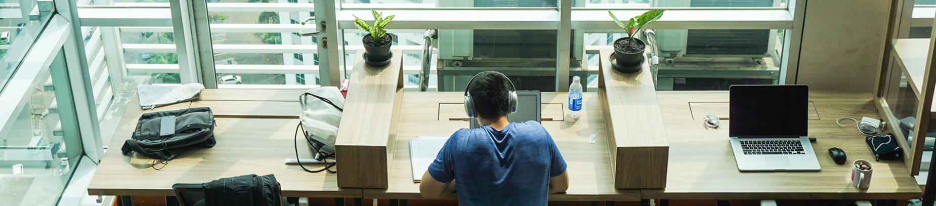 A man sat at a desk with headphones on