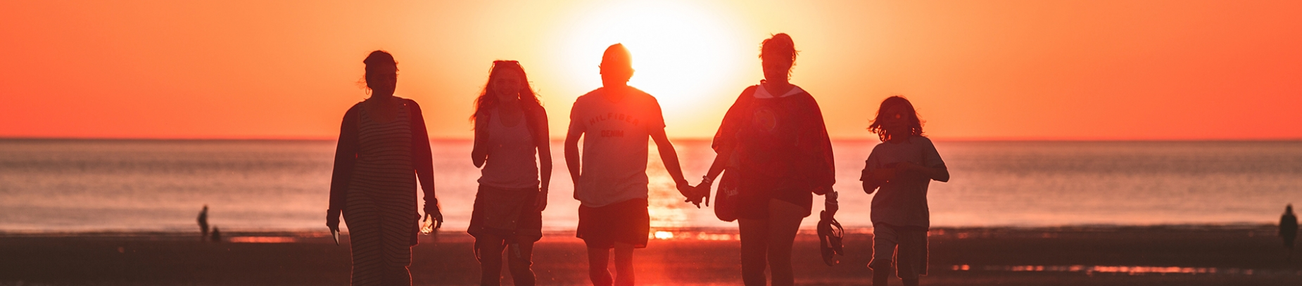 A family walking down the beach with the sunset behind them