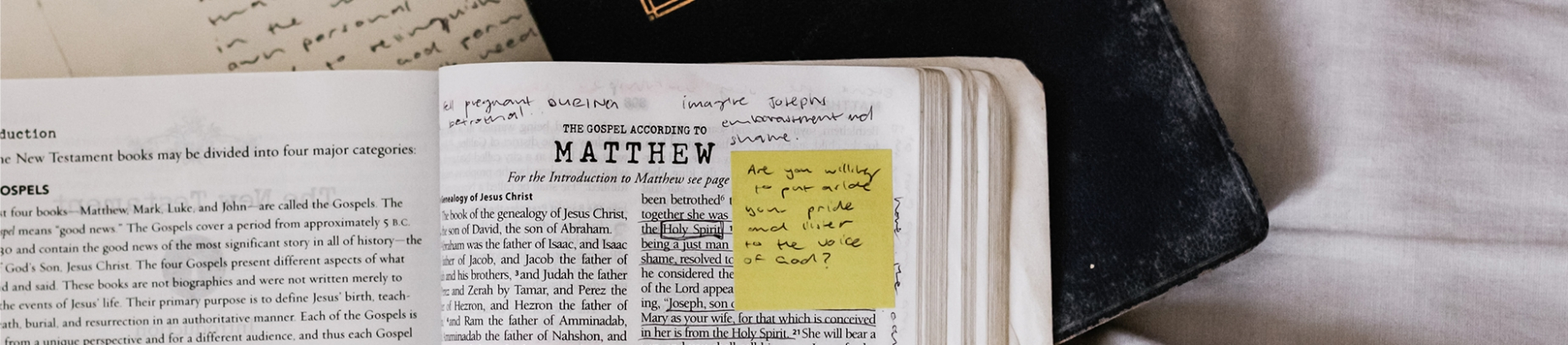 Open bible with notes and post-it note stuck on the page