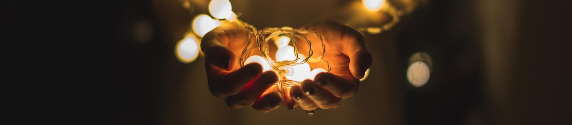 A women holding lit string light bulbs