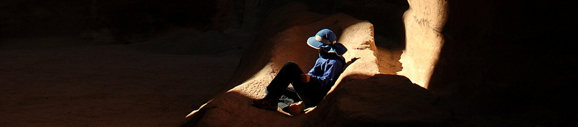 A guy sat in a cave with the light shining onto him