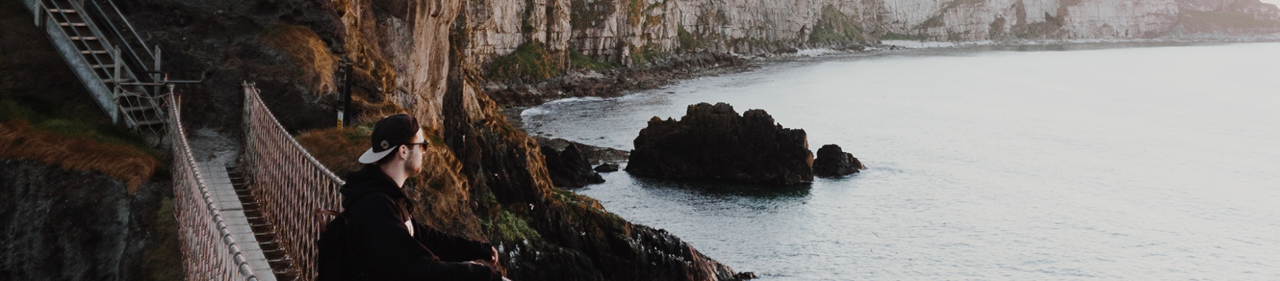 A guy stood on a rope bridge looking over the ocean