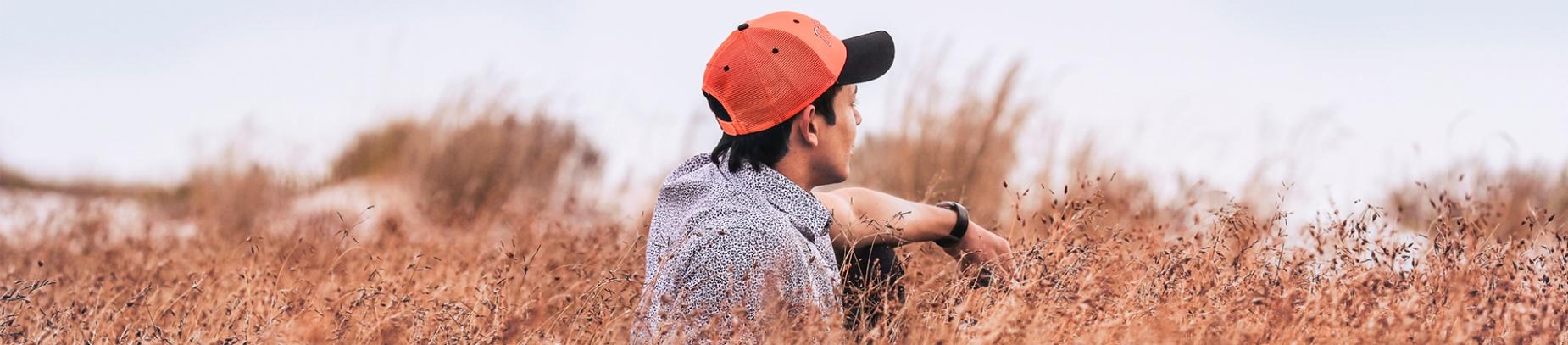 A man looking away sat in a field