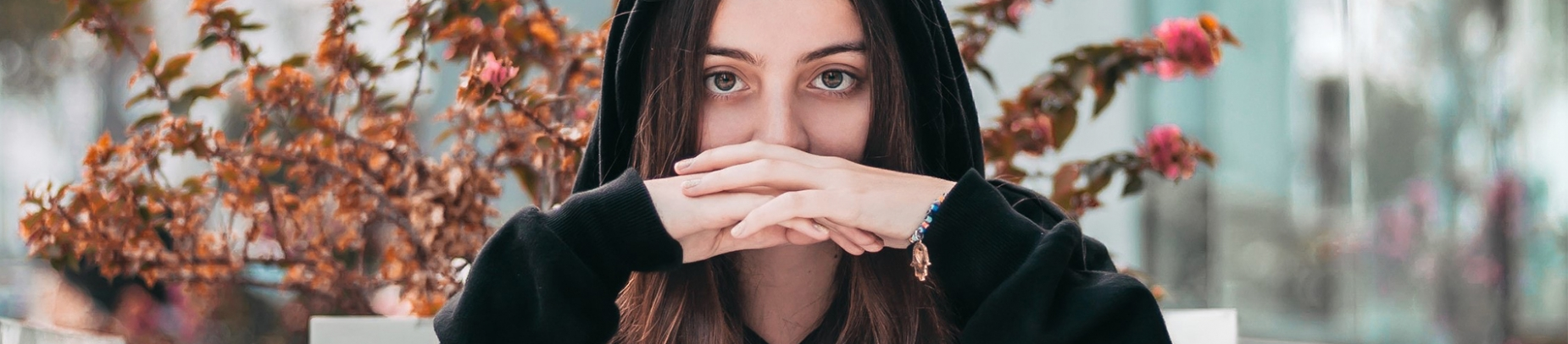 A woman with her hoodie hood up with her hands crossed in front of her