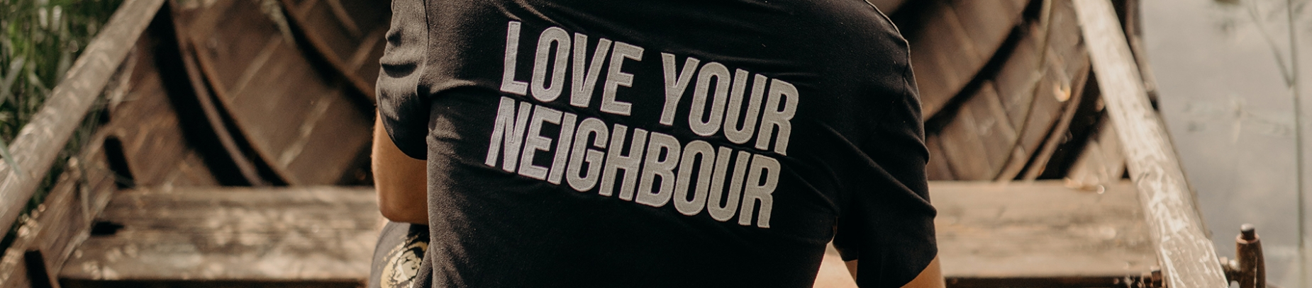 A man sat in a wooden boat wearing a 'Love Your Neighbour' top
