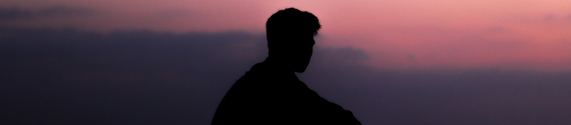 A silhouette  of a man looking towards a sunset sky