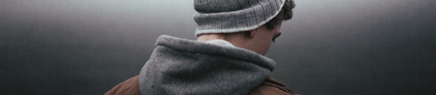 A guy in a beanie hat and hoodie looking down