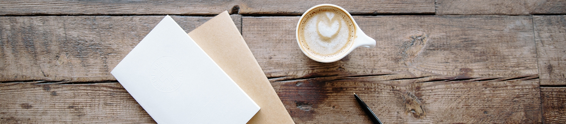 Wooden table with a blank card and envelope and a cup of coffee