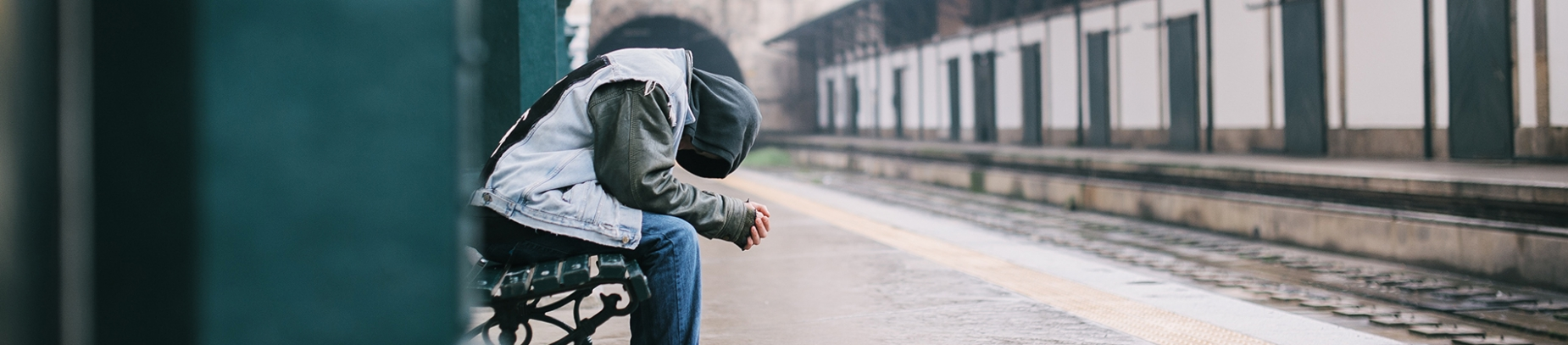 A man sat ay a train stop bowing his head into his hands