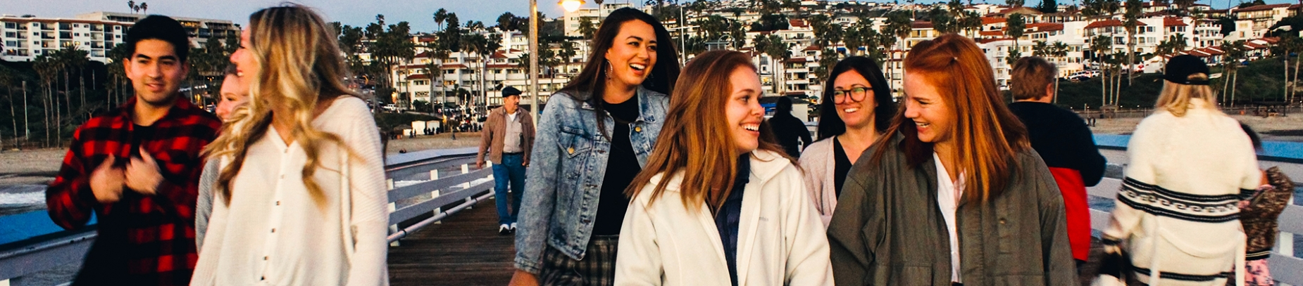 A group of friends smiling and talking while walking down a pier