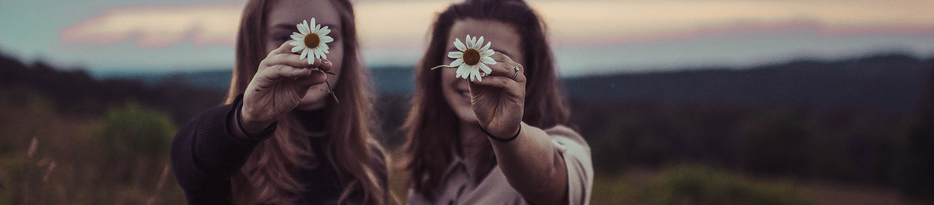 Two girls stood in a field holding up flowers in front of their faces