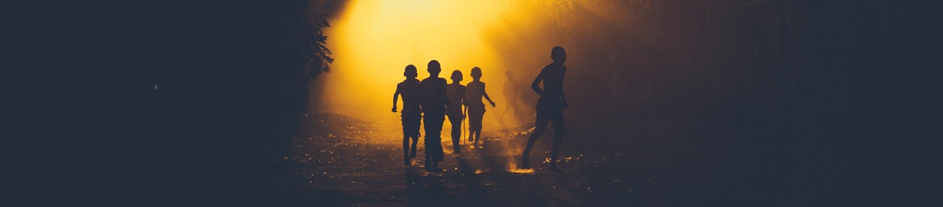 Children running down a sun lit road