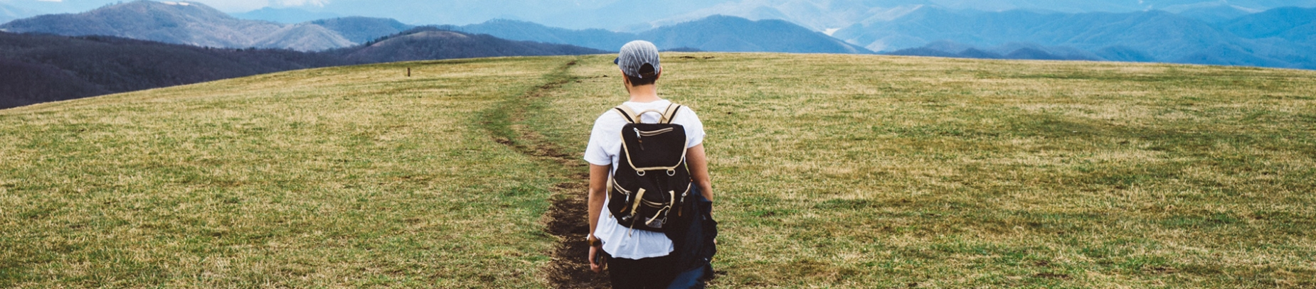 A guy walking down a grass path wearing a backpack