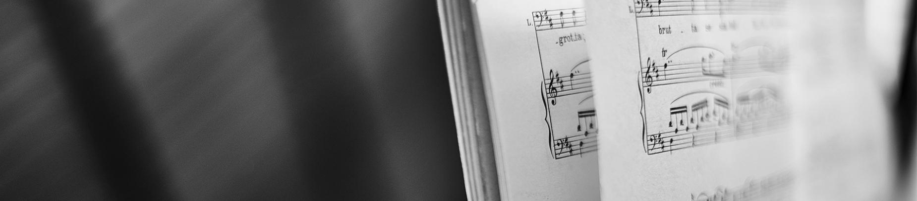 Sheet music stood up on a piano shelf