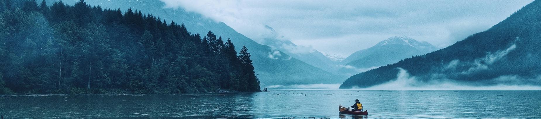 A man in a canoe rowing across a lake