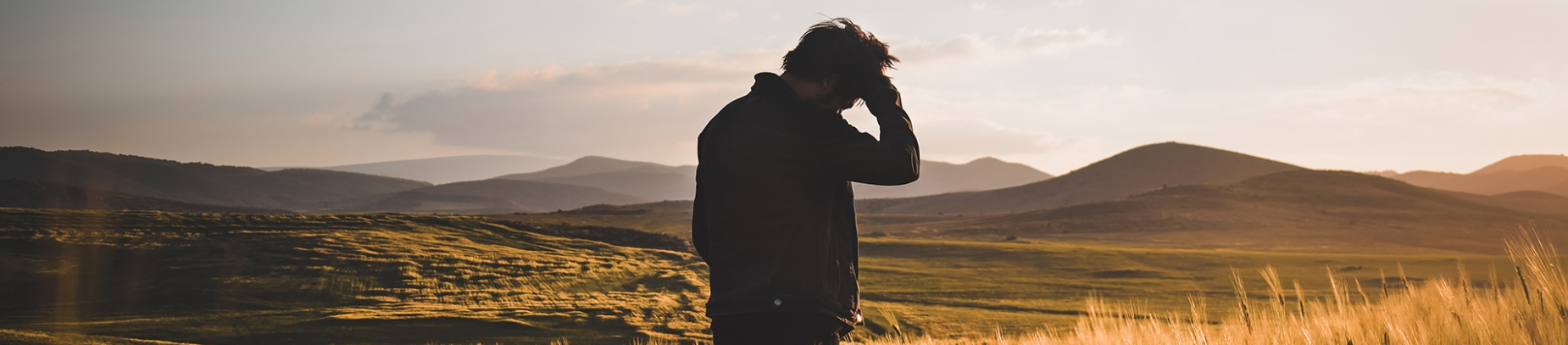 A man with his hand on his head looking out over a sunset and mountains