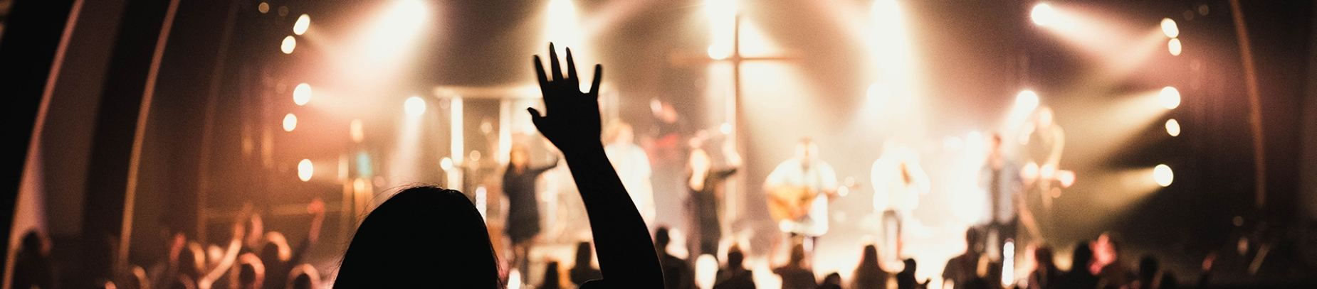 A church worship team on stage and a women with her hand in the air