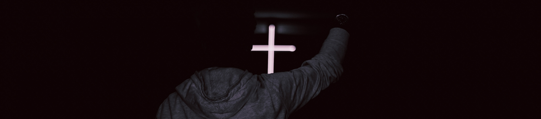 A guy with his arm up in praise in front of a glowing cross