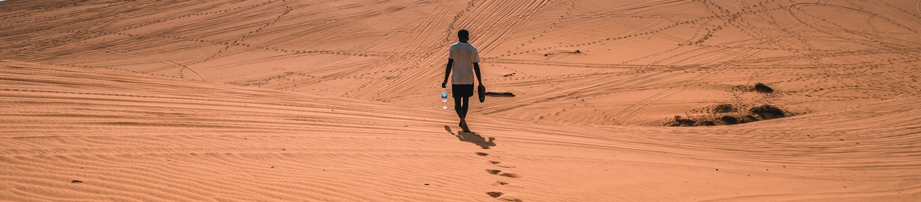 A man walking through the desert holding shoes and water