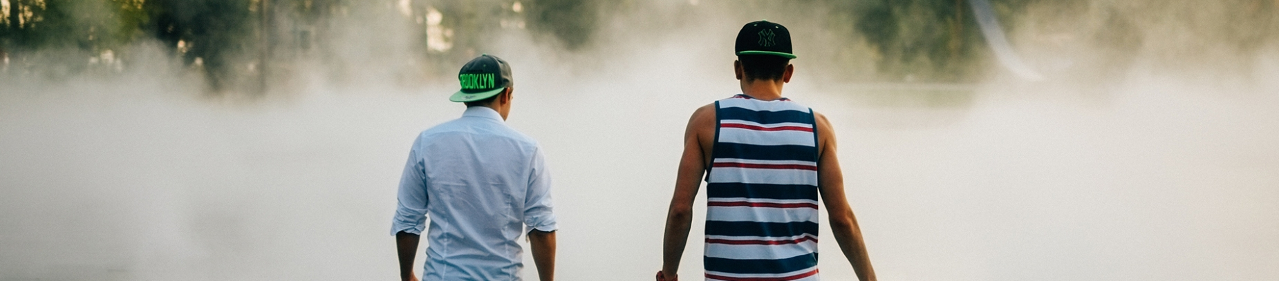Two men in baseball hats walking into a cloud of smoke