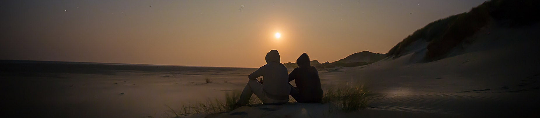 Two people sat on a beach watching the sunset