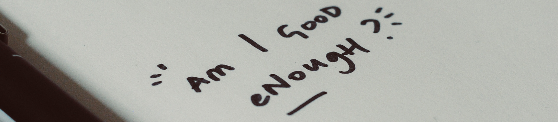 "A notebook with 'Am i good enough"" written on a page"