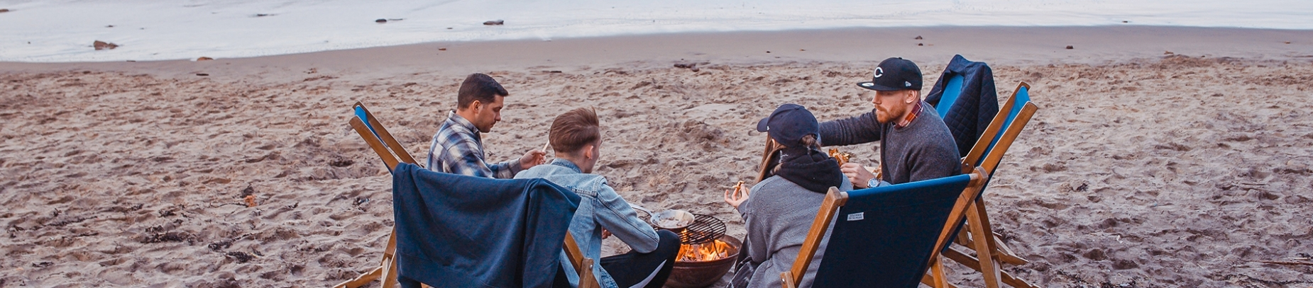 A group of friends sat around a fire on the beach