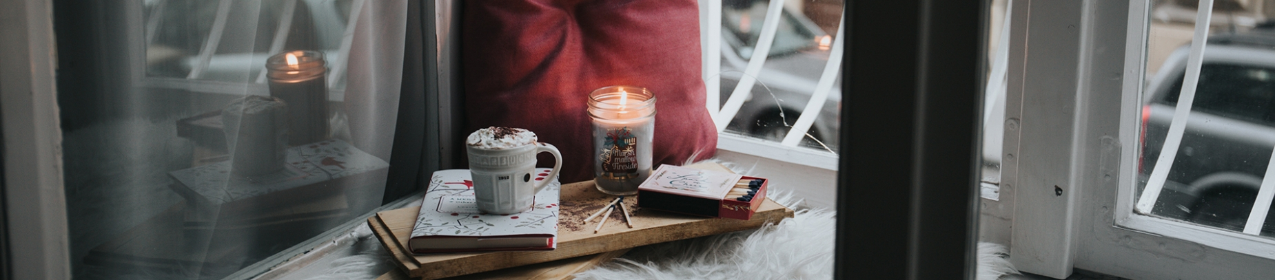 A cosy windowsill with a pillow, candle, hot chocolate and books