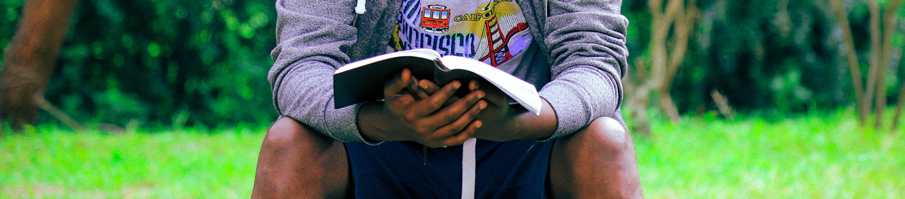A man sat in a park reading his bible
