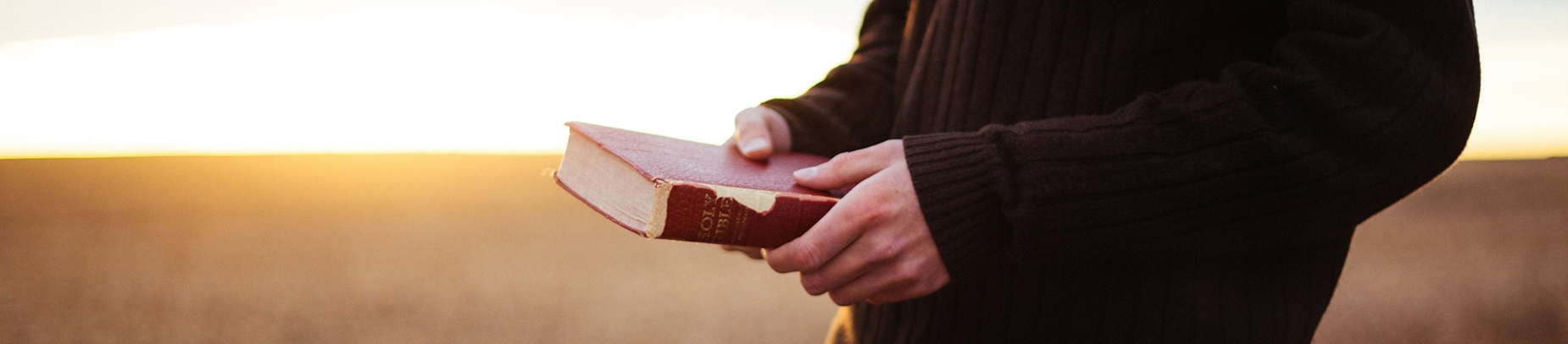 A guy in a jumper holding a brown bible