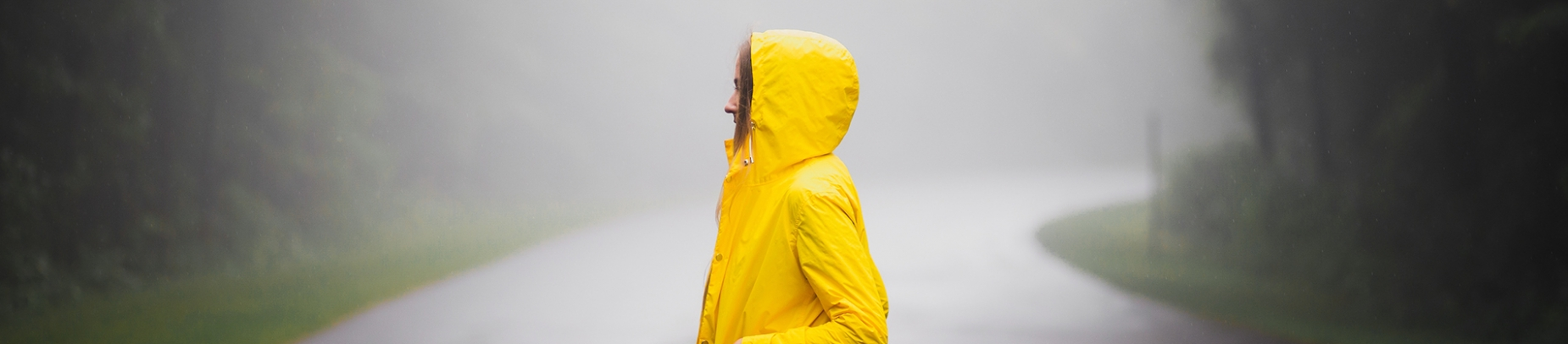 A girl in a bright yellow coat stood on a road in the rain and mist