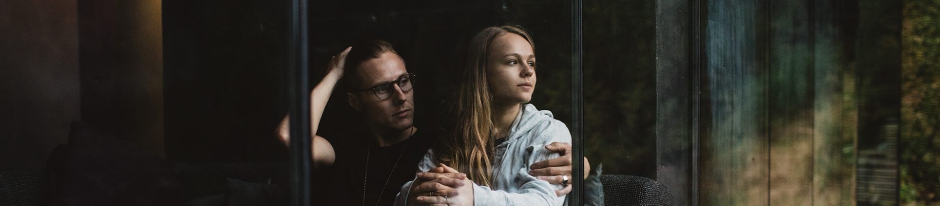 A couple sat looking out of a glass window