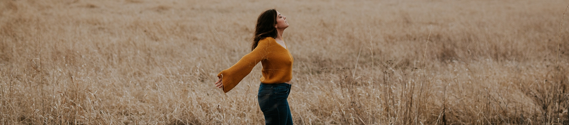 A women in a orange jumper stood in a field with her arms out wide
