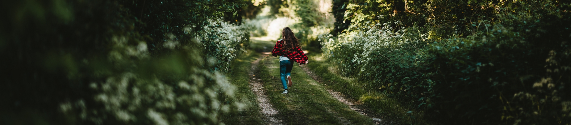 A girl in a red top running down a path into a forest