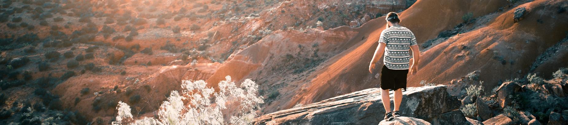 A man climbing over rocks down a hill