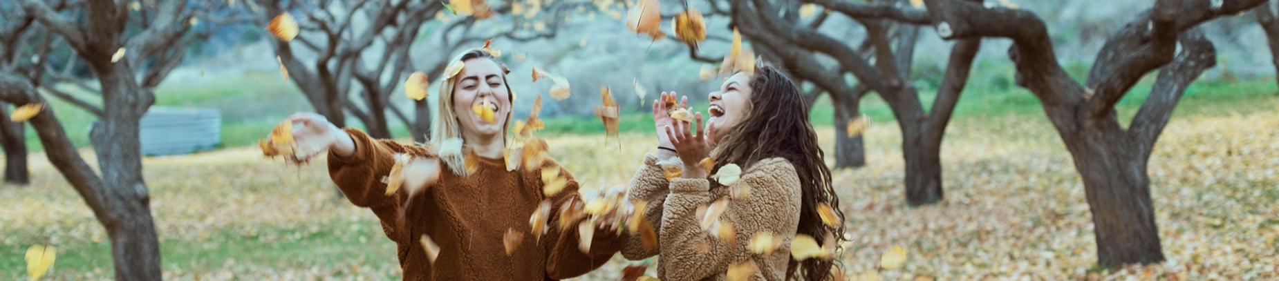 Two women in a park, throwing leaves into the air and laughing
