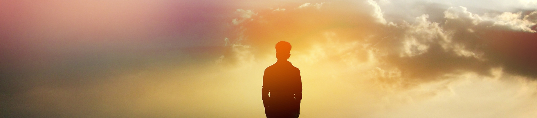Silhouette of man with coloured sunrise in front of him