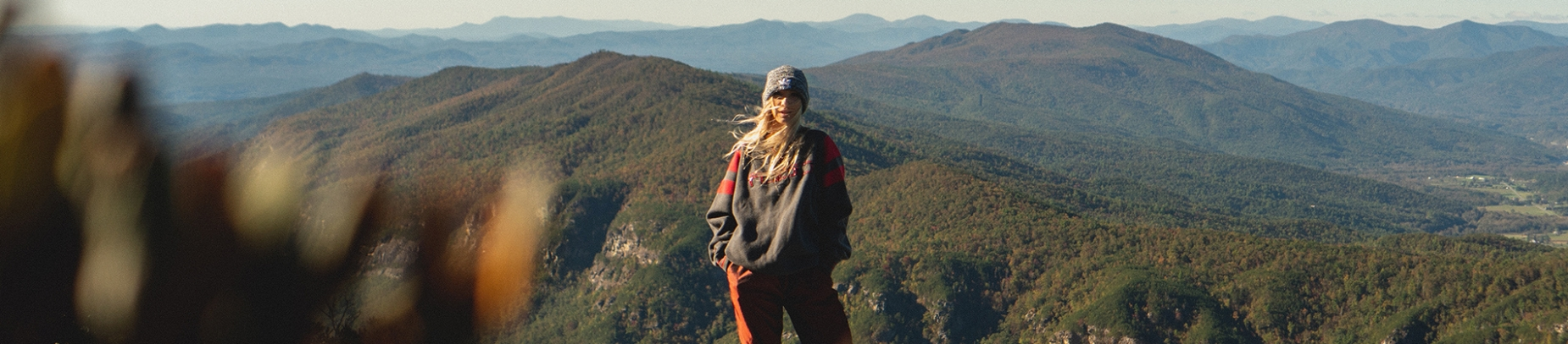 A women stood on top of a mountain with her hair blowing in the wind
