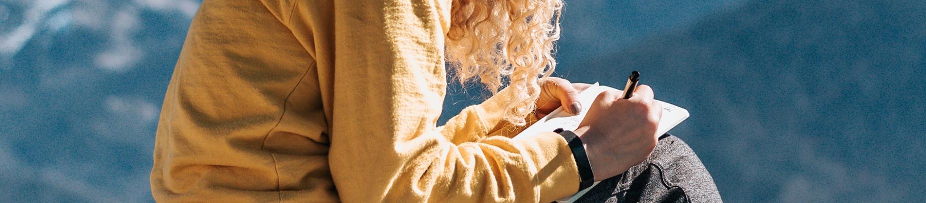A women sat writing in a notebook