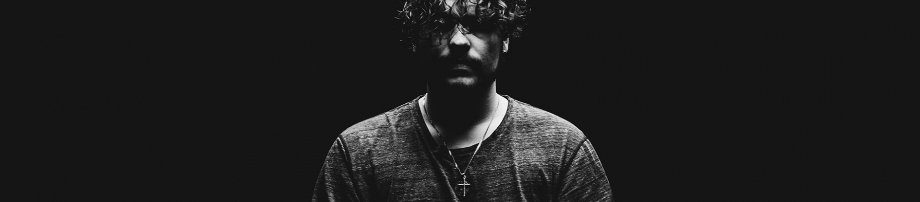 A black and white photo of a guy wearing a cross necklace looking hopeless