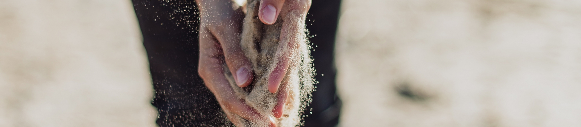 A person tipping sand through their hands on a beach