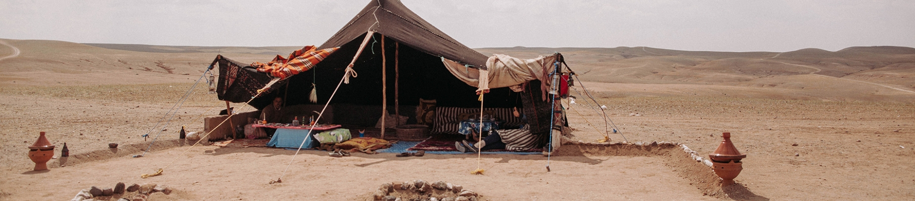 A old tent held up with ropes in the middle of a desert
