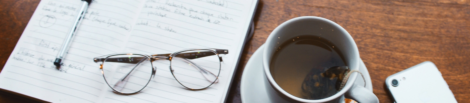 An open notebook and pen on a wooden table with a cup of tea, phone and glasses