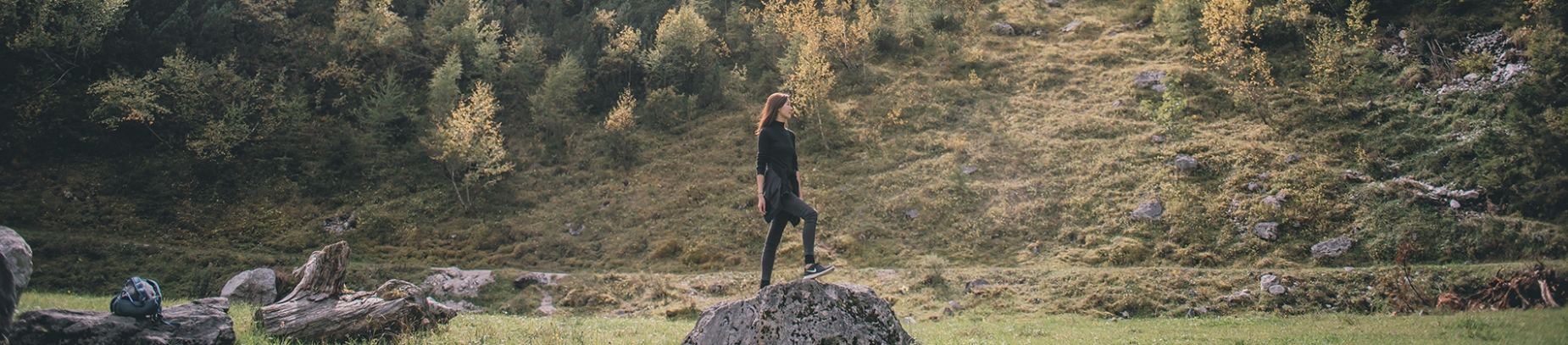 A women stood on top of a large rock in a field