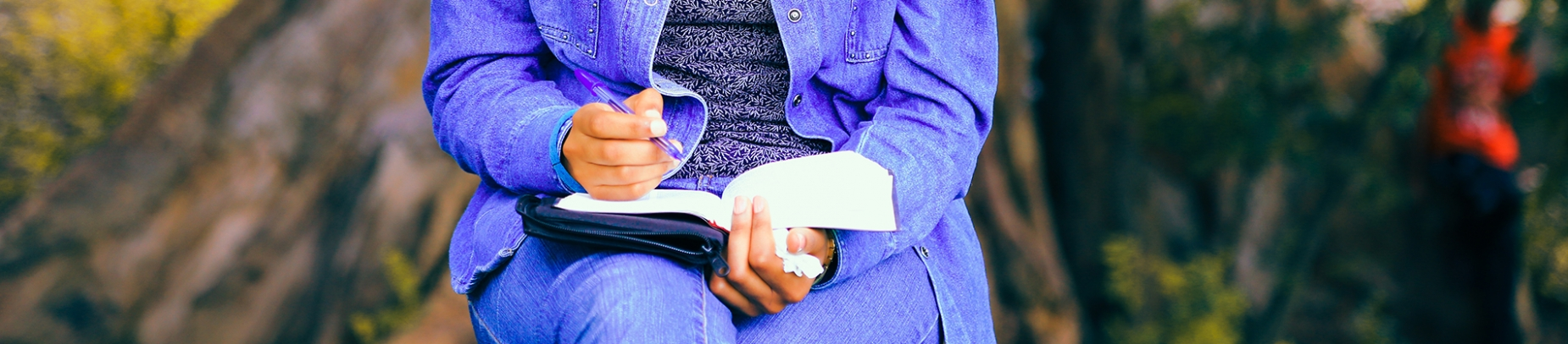 A women sat in a park writing in her bible