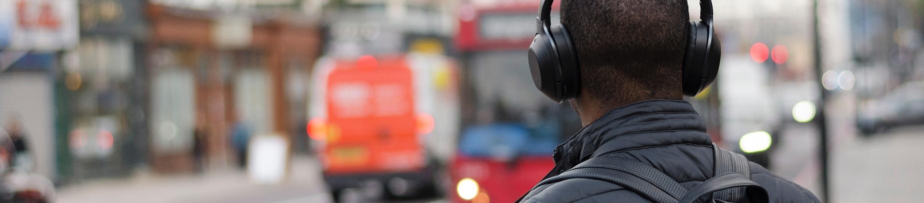 A man wearing headphones walking down a street
